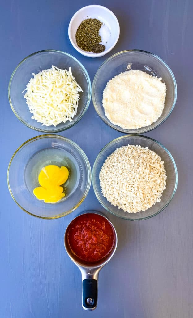 marinara sauce, breadcrumbs, an egg, mozzarella cheese, and parmesan cheese in separate bowls