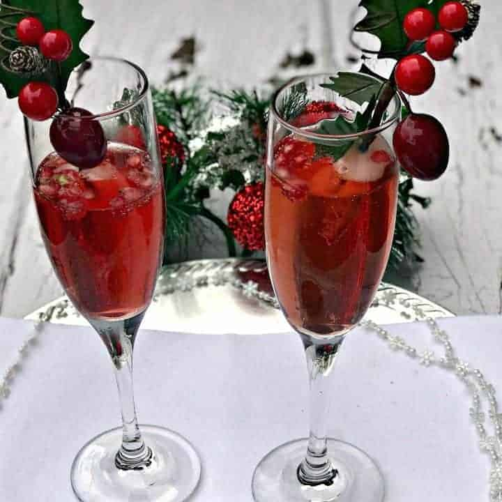 2 champagne flutes containing pomegranate mimosas, pomegranate seeds, and holiday decor