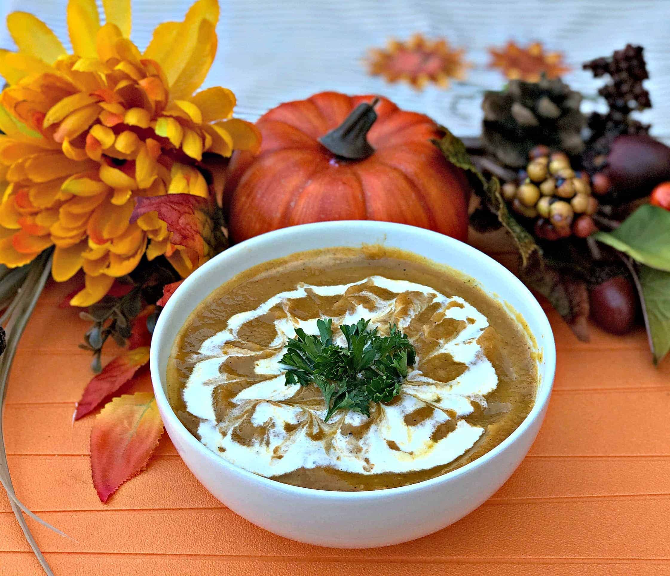 Instant Pot Pumpkin Spice and Sweet Potato Soup in a white bowl with fall decor in the background