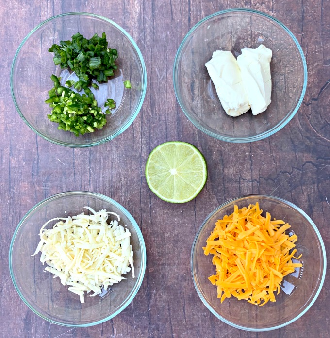 ingredients for keto low carb jalapeno popper chicken including chopped jalapeno, cream cheese, shredded cheese, and fresh lime