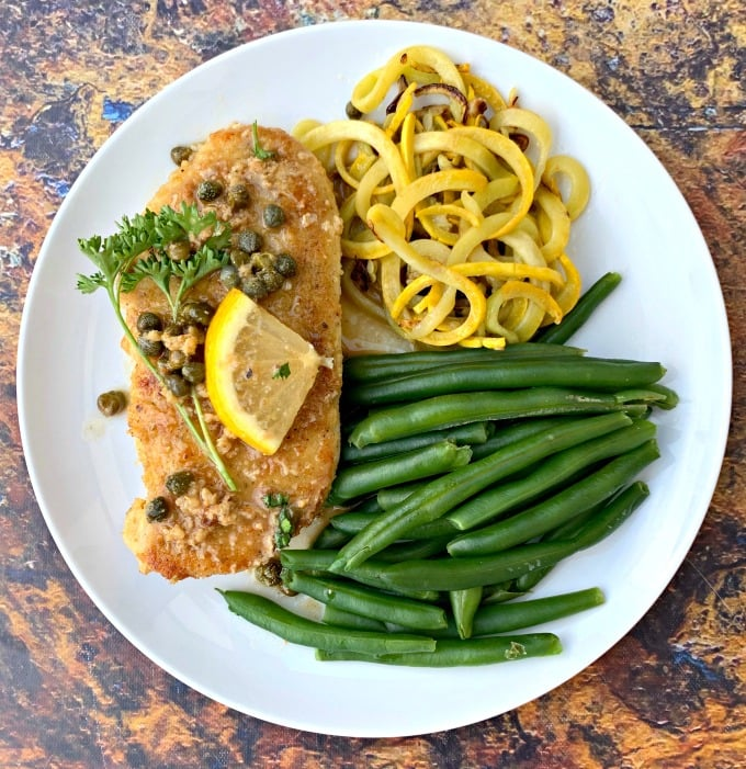 keto lemon chicken piccata on a white plate with green beans and squash