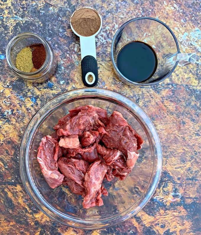 raw steak in a bowl with fajita seasoning and marinade