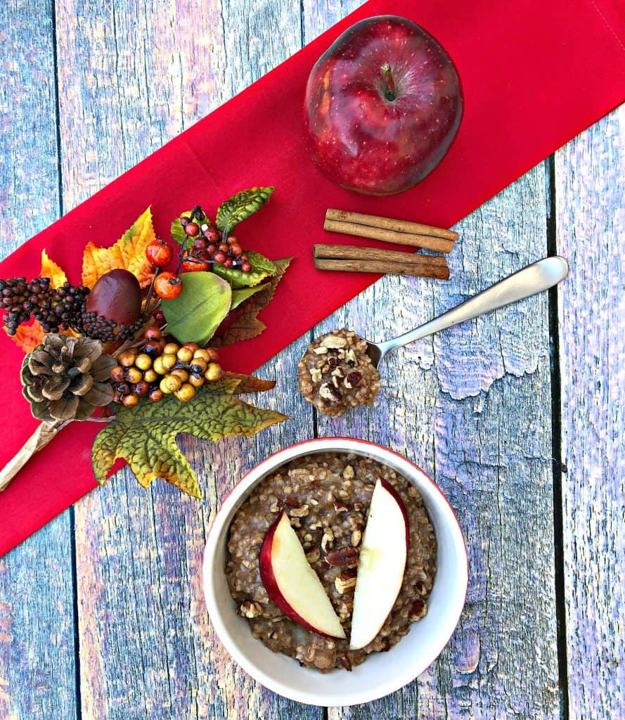 Instant Pot Apple Pie Steel Cut Oats in red bowls with a fresh apple and red napkin