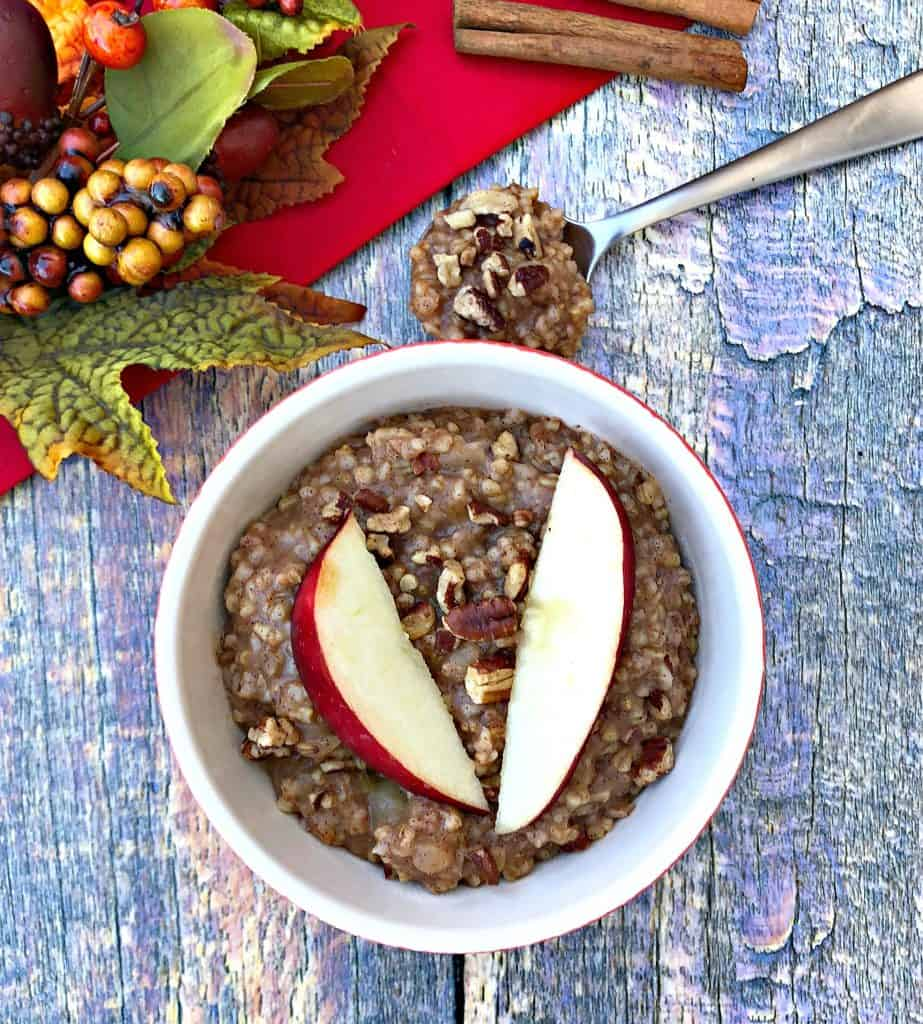 Instant Pot Apple Pie Steel Cut Oats in a red bowl with a fresh apple and red napkin