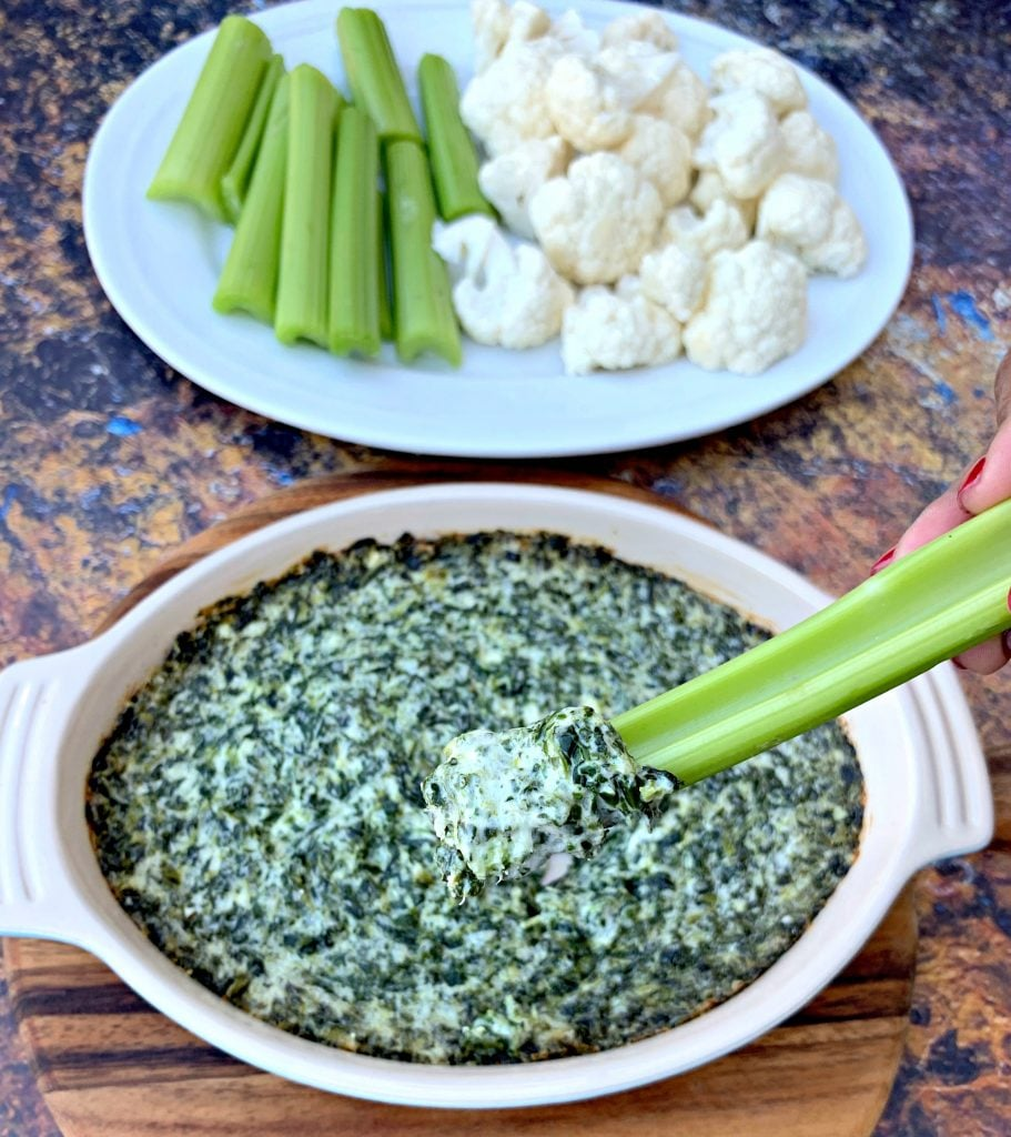 person holding celery with keto low carb spinach dip in a bowl with vegetables on a white plate