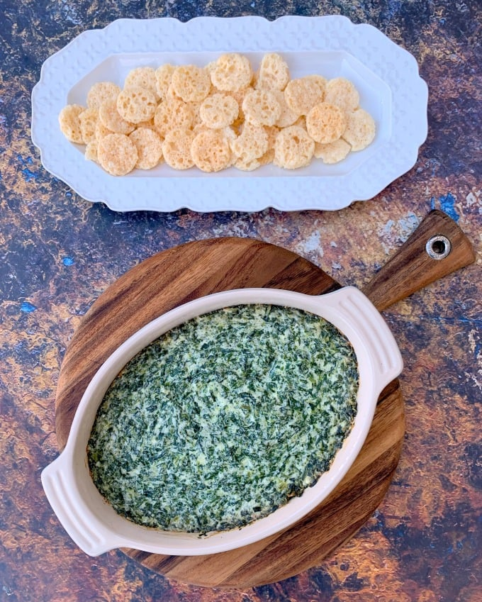 keto low carb spinach dip in a bowl with cheese crisps on a white plate