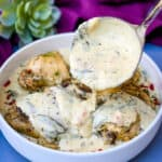 Instant Pot Low-Carb Creamy Garlic Tuscan Chicken Thighs in creamy sauce with parsley in a blue bowl