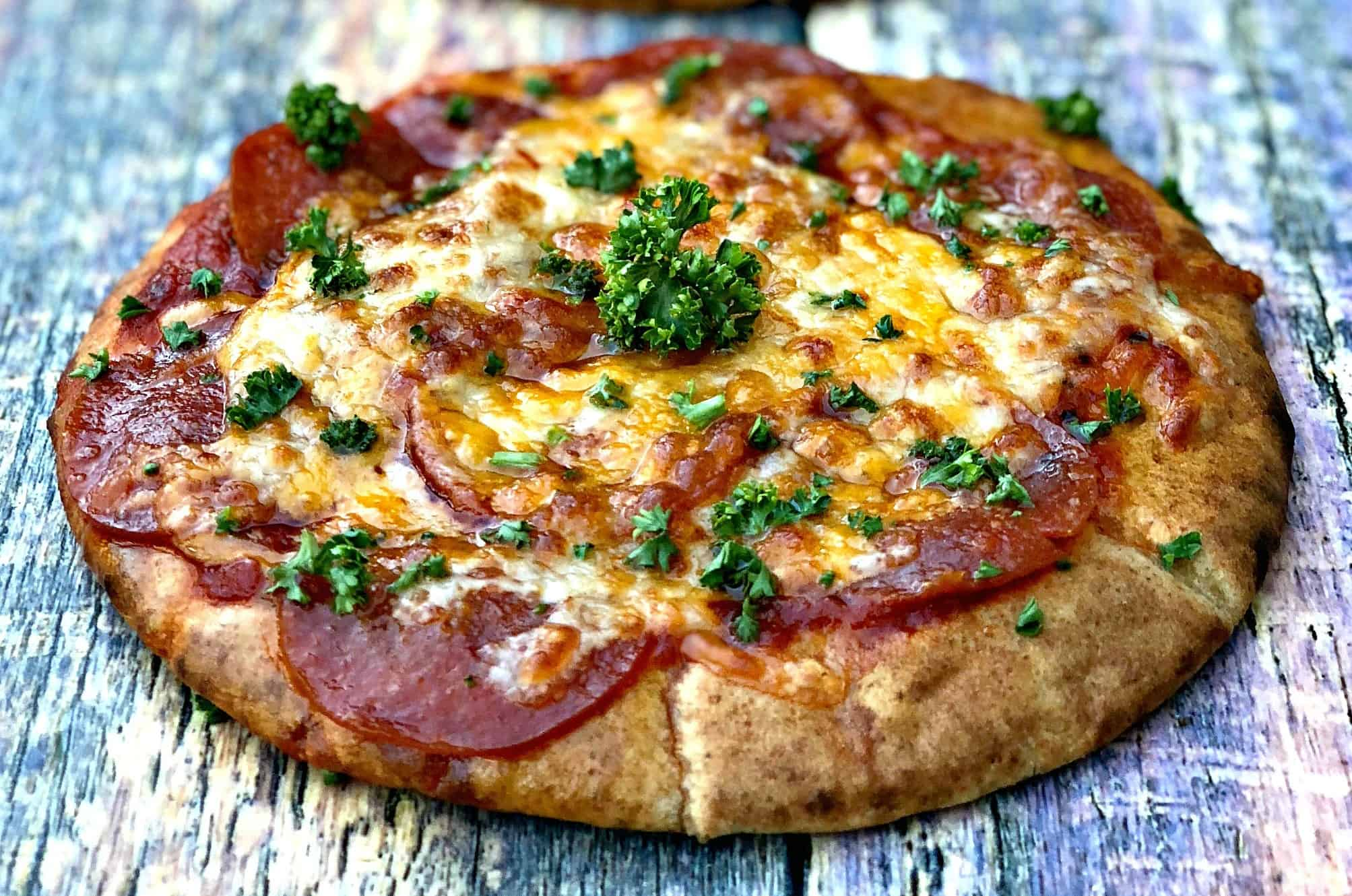 close up of air fryer pepperoni pizza with mozzarella cheese on a multi colored surface