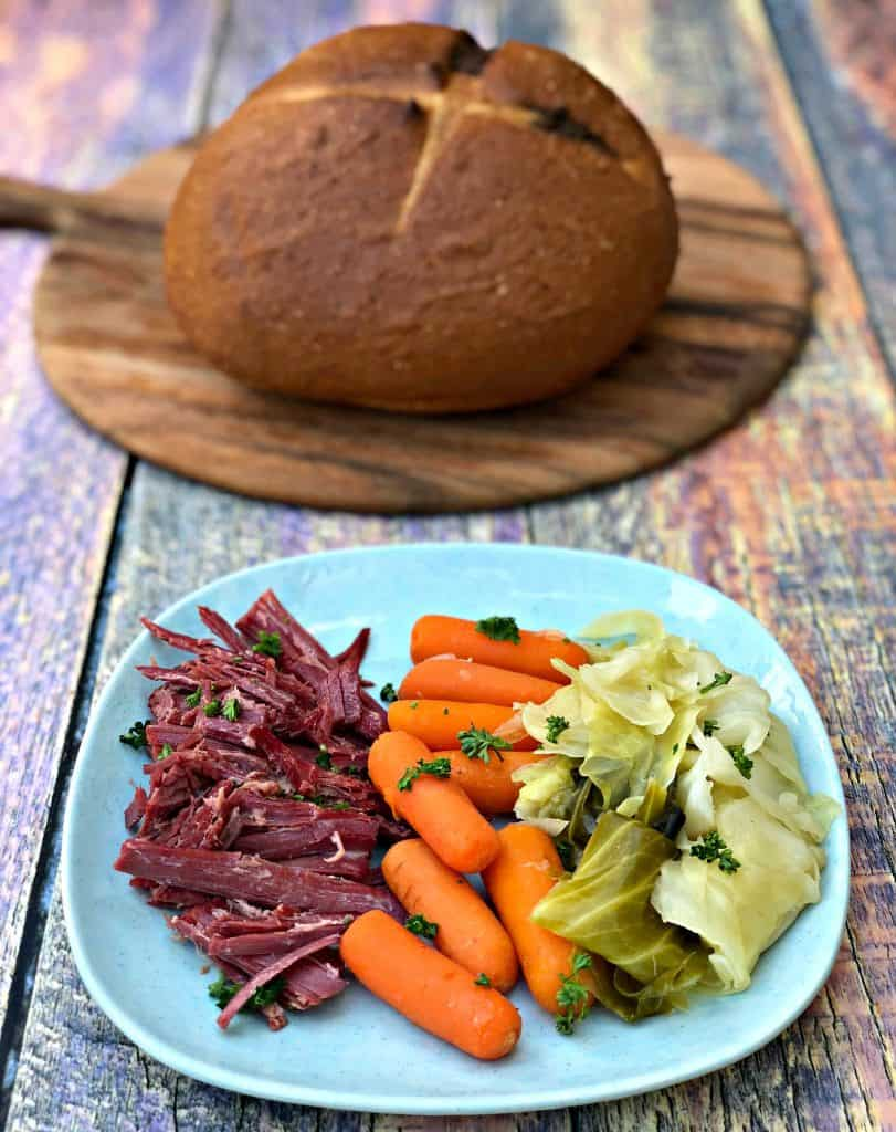 corned beef, carrots, and cabbage on a blue plate with rye bread