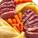 corned beef, carrots, and cabbage in a blue bowl with rye bread