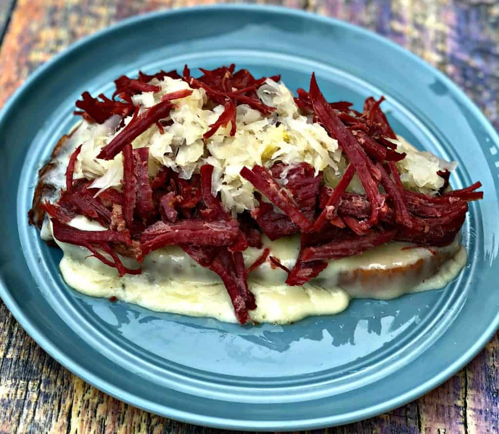 Instant Pot Corned Beef Reuben Sandwich with rye bread, sauerkraut, and thousand island dressing on a blue plate