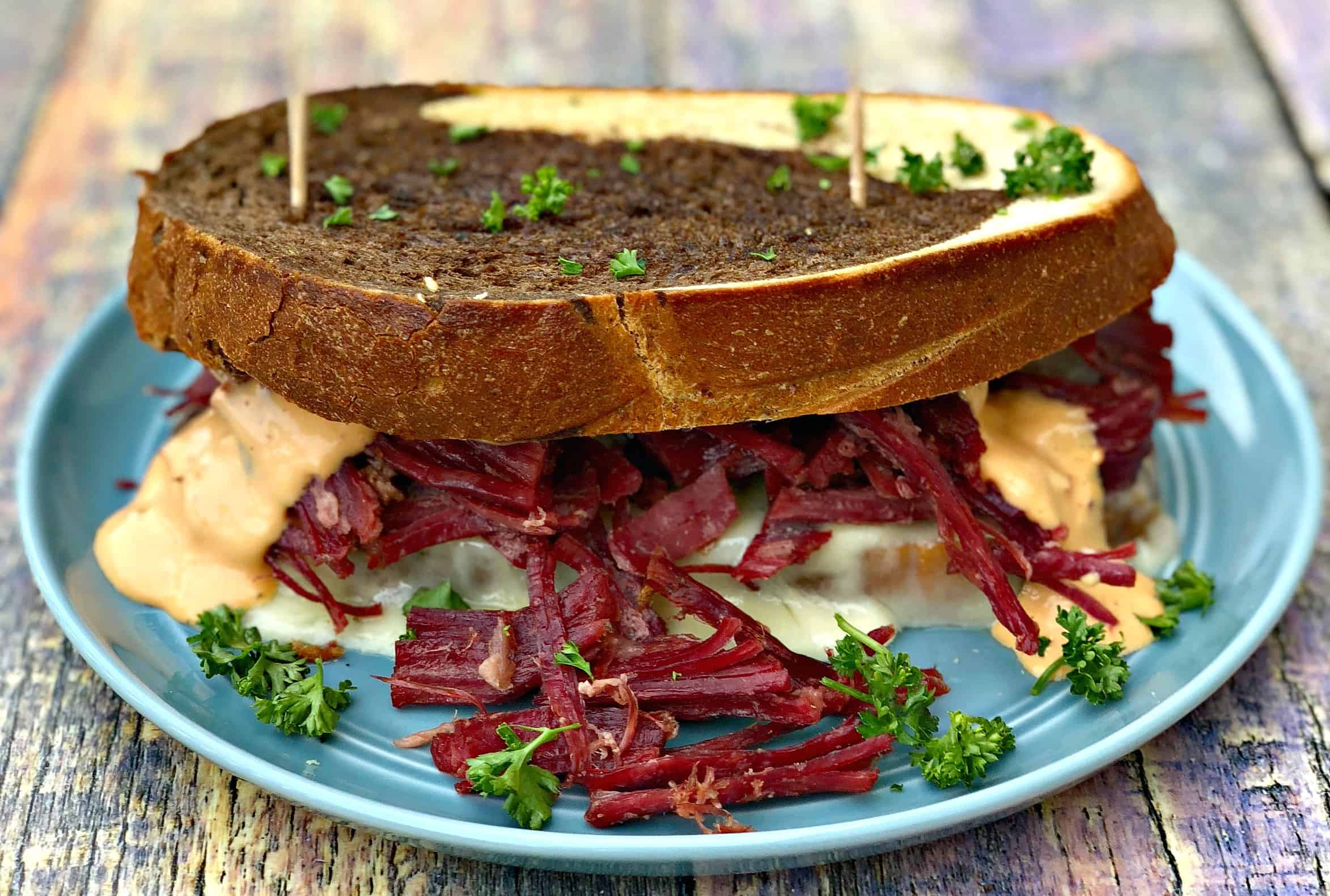 close up of Instant Pot Corned Beef Reuben Sandwich with rye bread, sauerkraut, and thousand island dressing on a blue plate