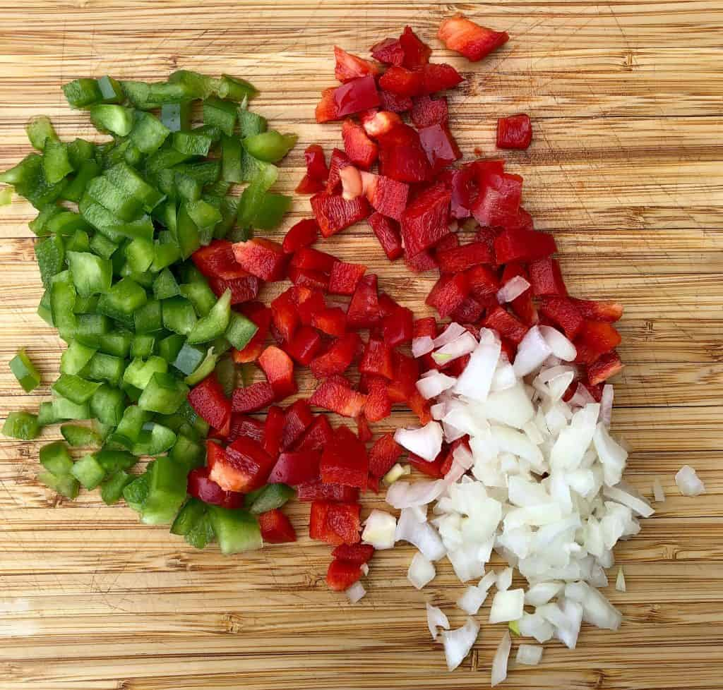 chopped red and green peppers and chopped onions on a cutting board