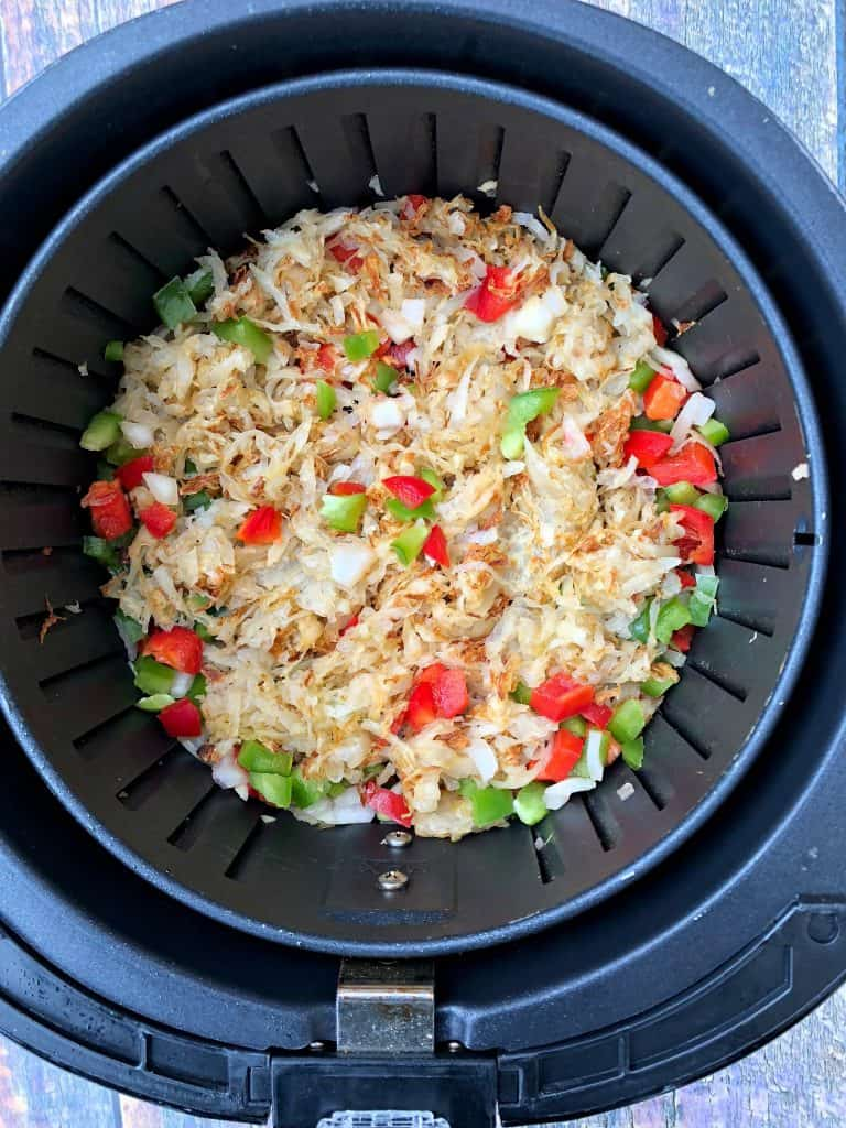 hashbrowns in an air fryer with chopped vegetables