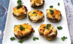 cooked stuffed mushroom with cheese on a white plate
