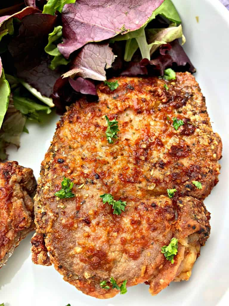 air fryer pork chops in a white bowl with salad