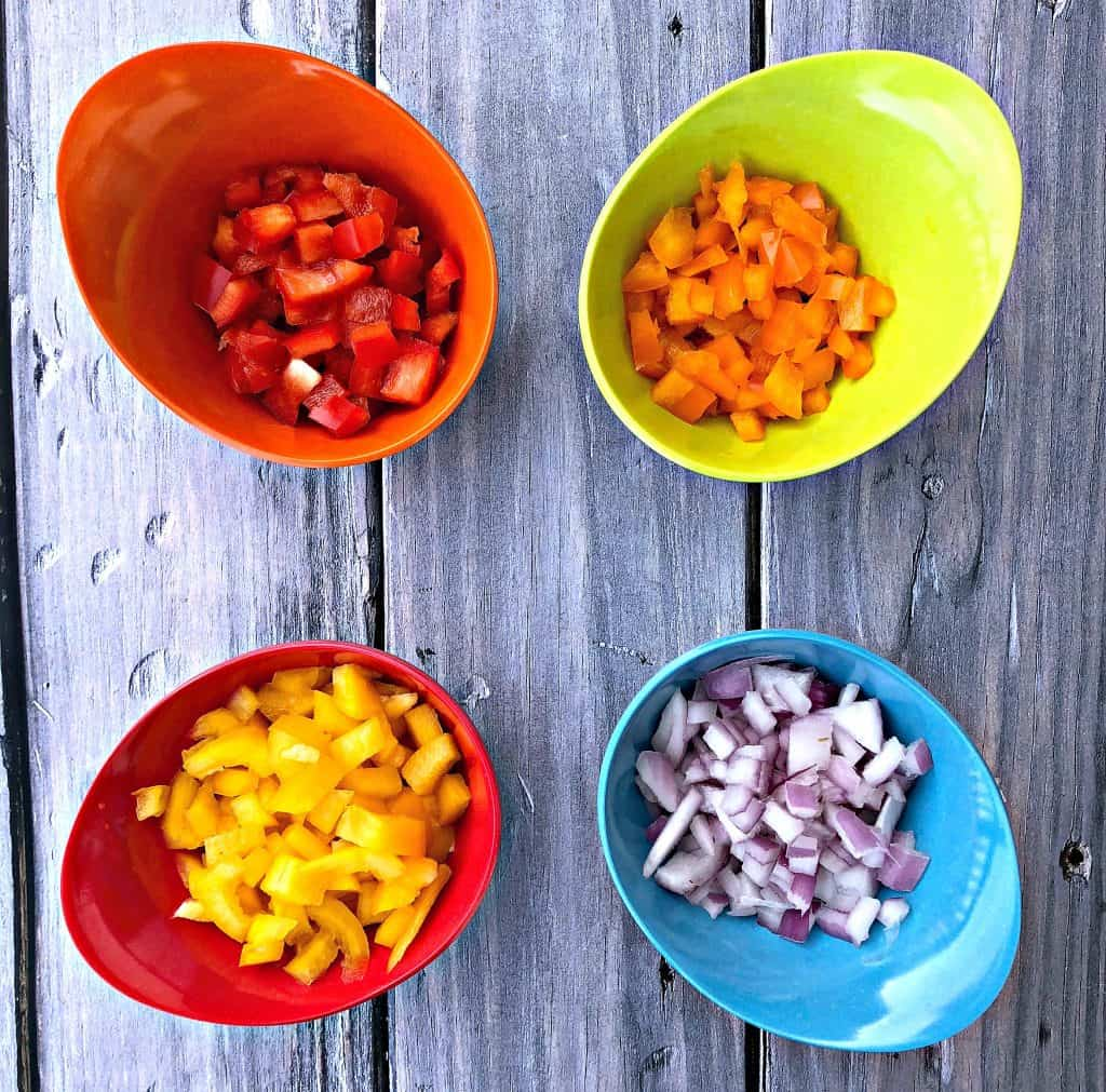 red, orange, and yellow peppers diced in multi colored bowls and red onions in a blue bowl