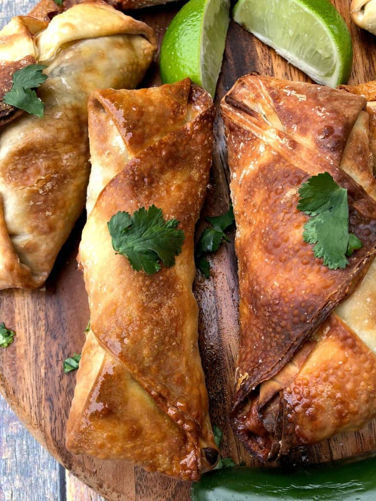 air fryer southwestern egg rolls spread out on a brown cutting board