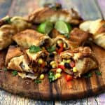 air fryer southwestern egg rolls cut in half with black beans, corn and red peppers spread out on a brown cutting board