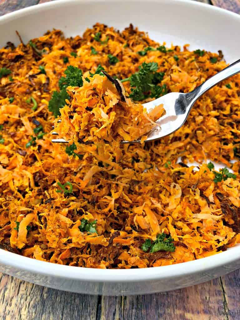 sweet potato hash browns scooped with a fork in a white bowl