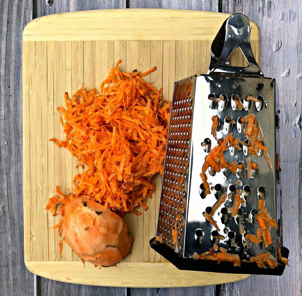raw sweet potato shredded next to a cheese grater