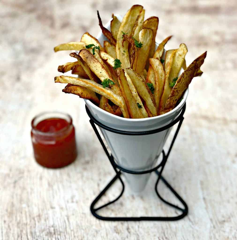 air fryer fries spread out on a brown surface with ketchup