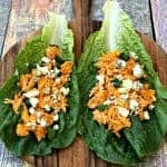 buffalo chicken wraps on romaine lettuce on a cutting board with blue cheese