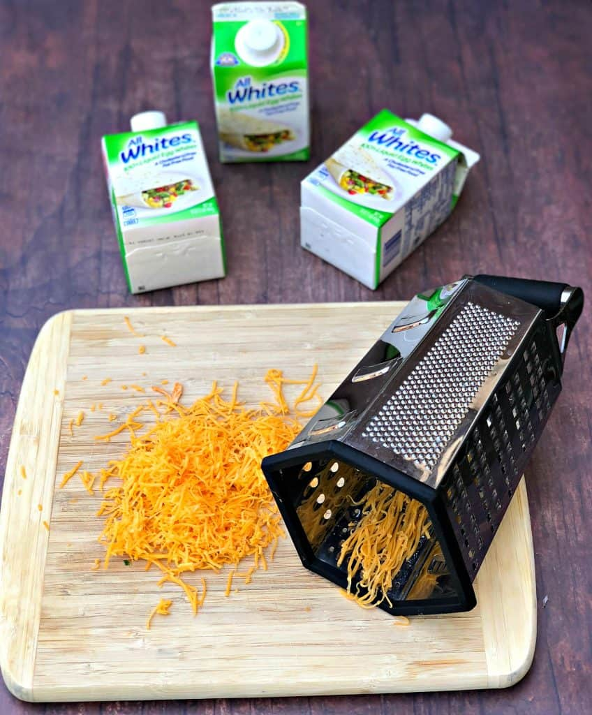 shredded cheese on a cutting board with a cheese grater