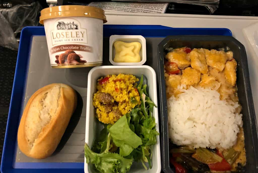 airplane meal with thai food and a roll