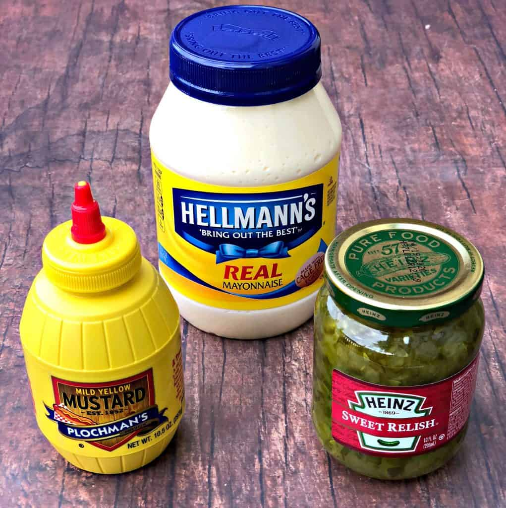 mayo, mustard, and relish in jars on a brown surface