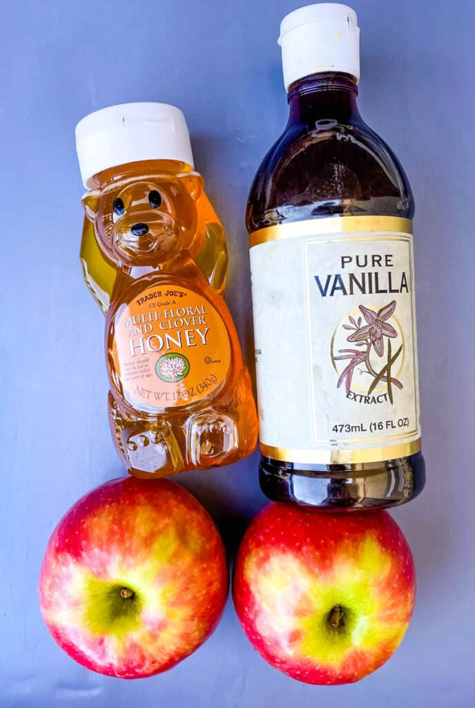 a bottle of honey, a bottle of vanilla, and fresh apples