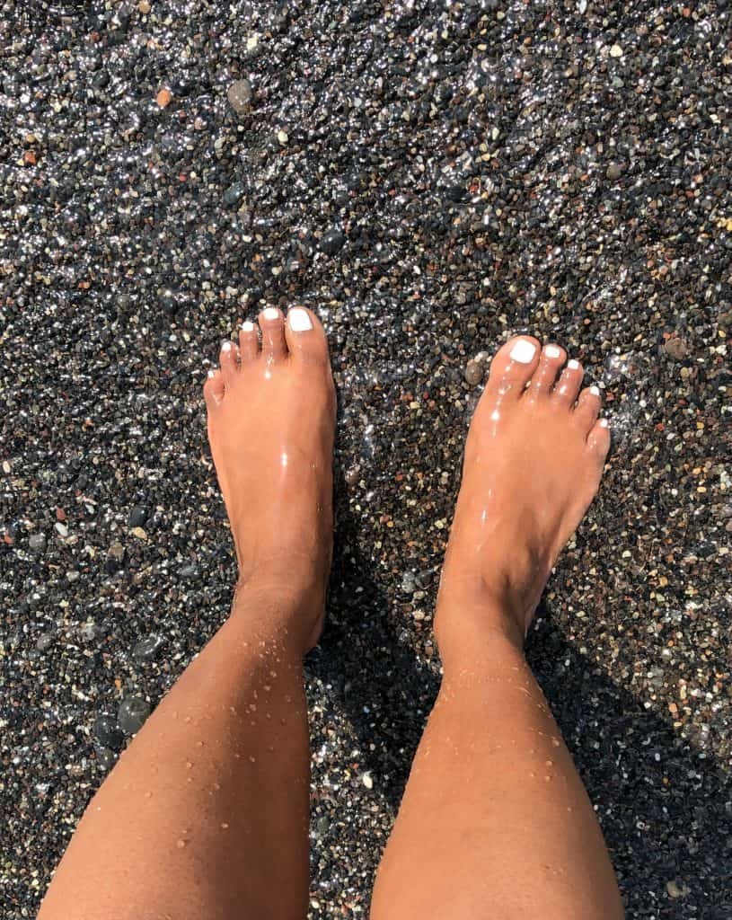 feet in black sand in santorini