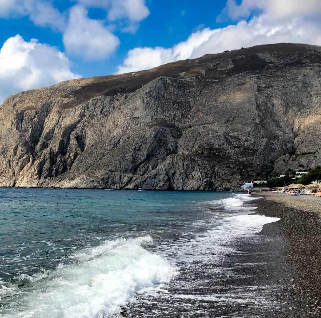 santorini black beach with the waves of the sea