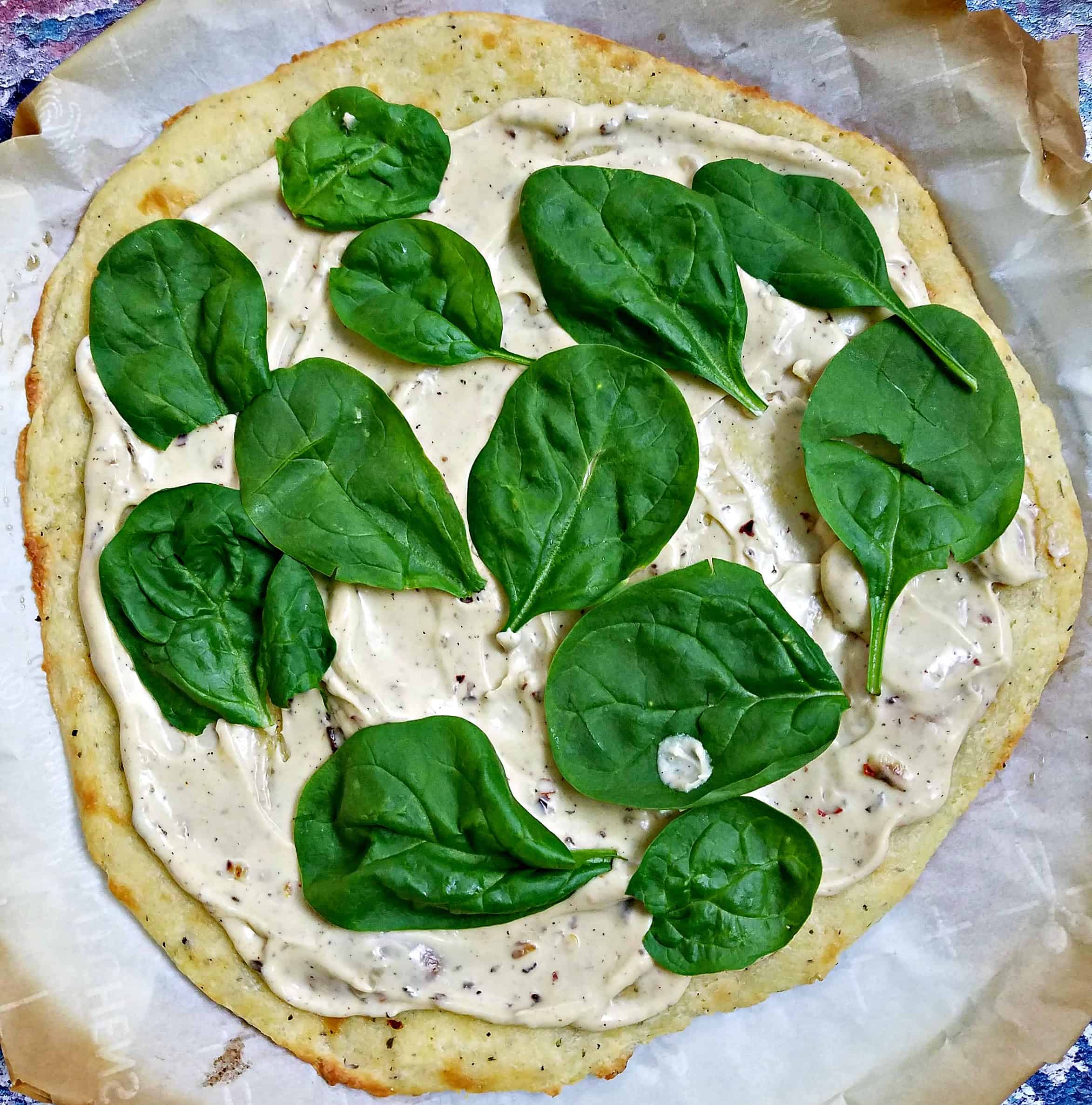 uncooked pizza with spinach