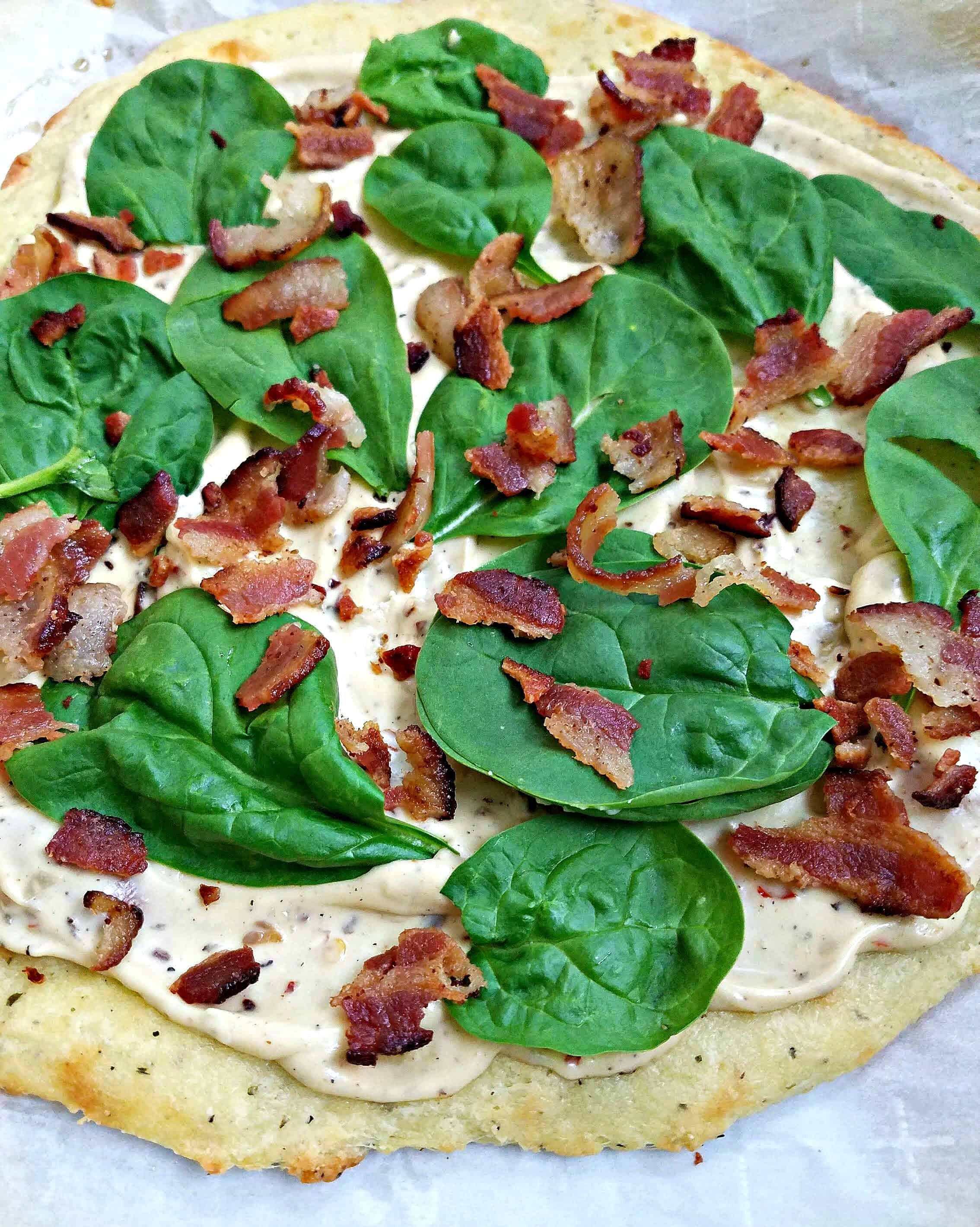 uncooked pizza with spinach and bacon
