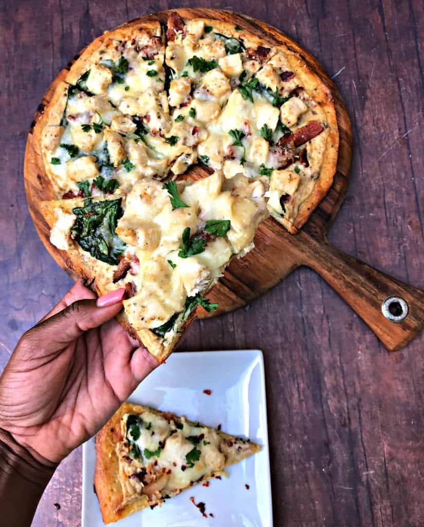 person holding slice of keto fathead alfredo bacon chicken pizza on a pan