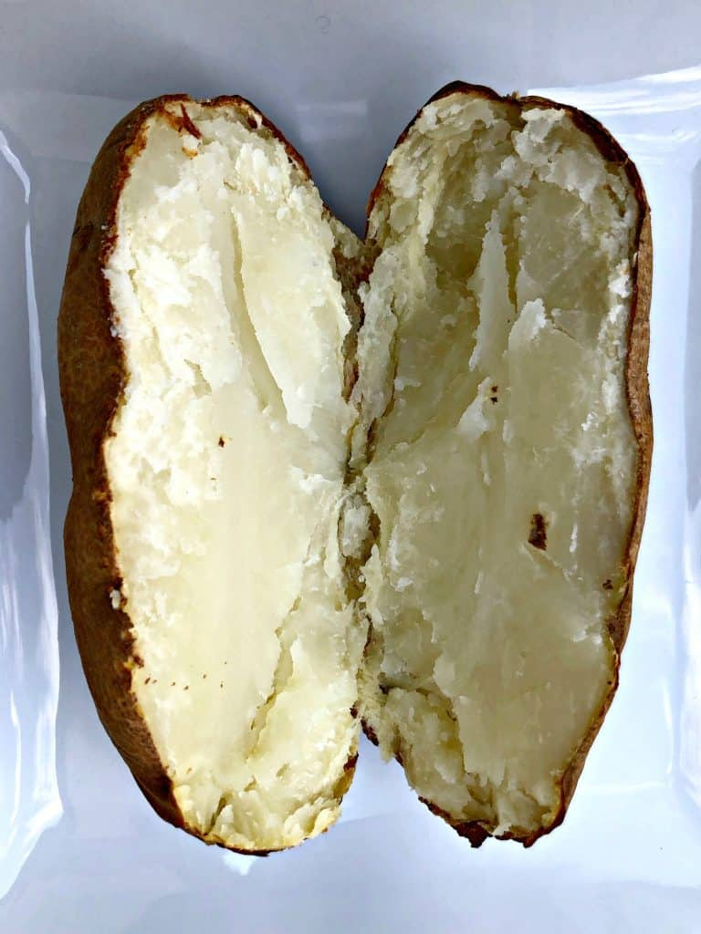 baked potato sliced in half on a white plate