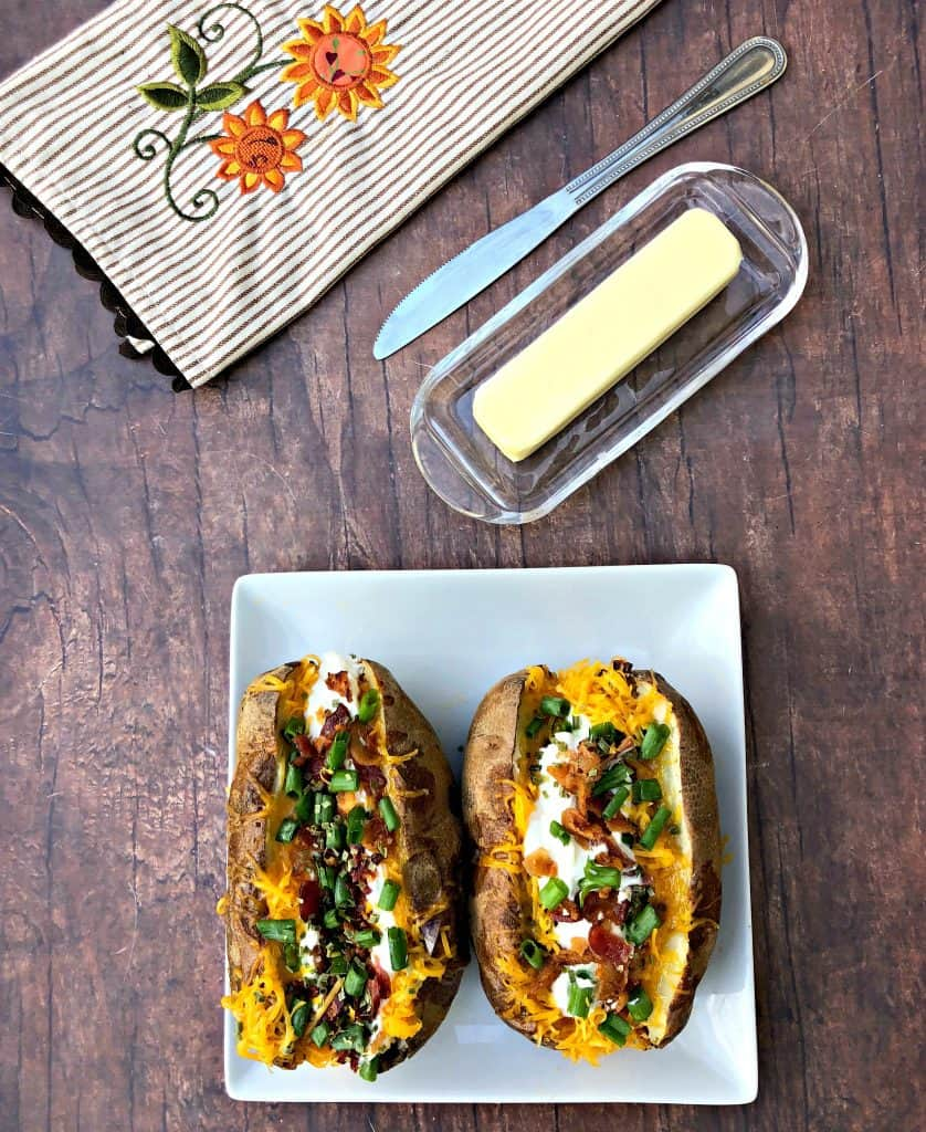air fryer loaded baked potato on a plate with butter