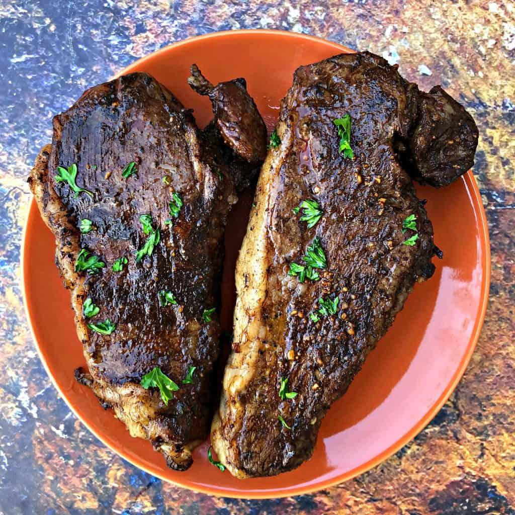 air fryer steaks on an orange plate