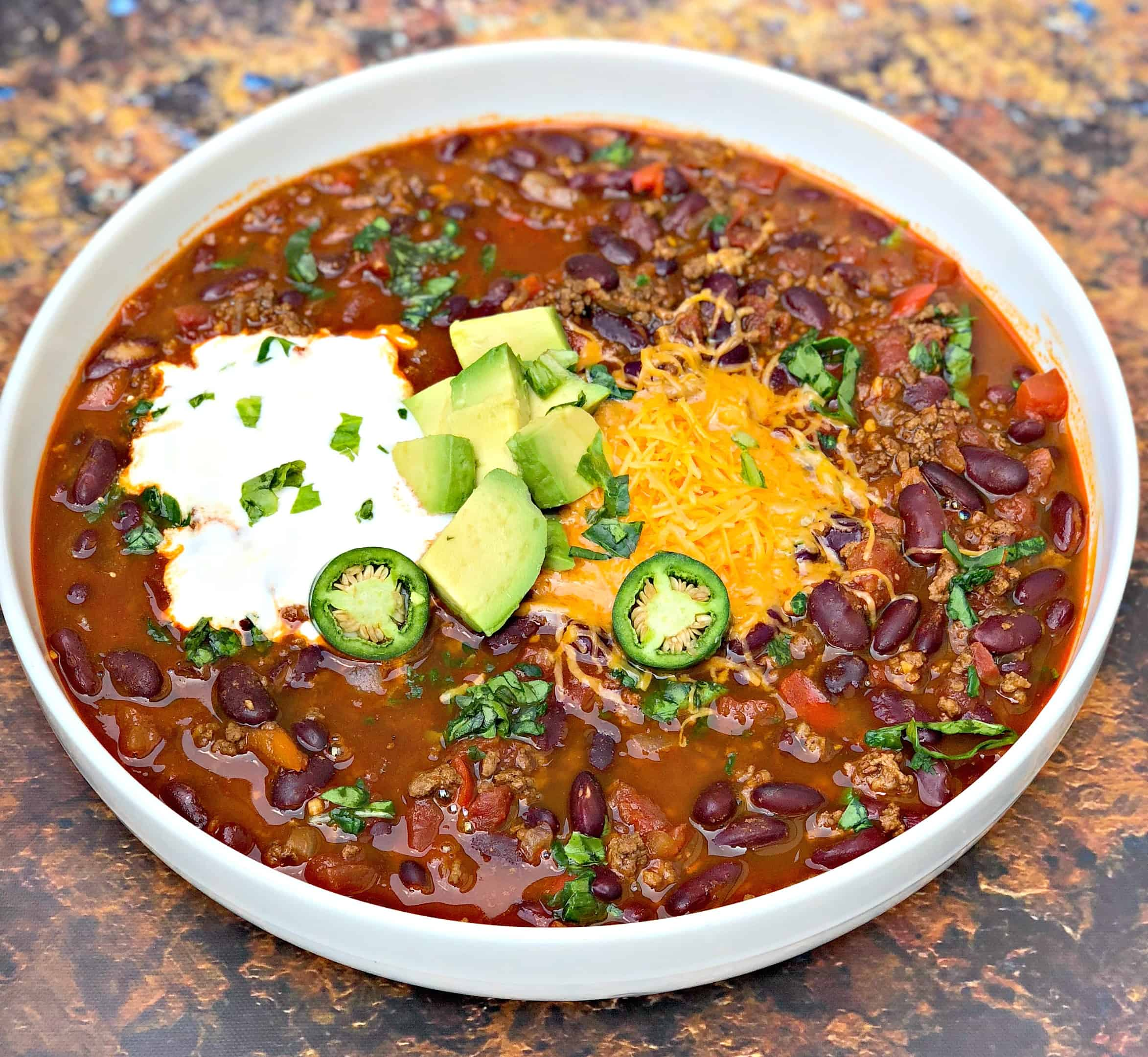 instant pot chili with shredded cheese, avocado, sour cream and jalapeno served in a white bowl