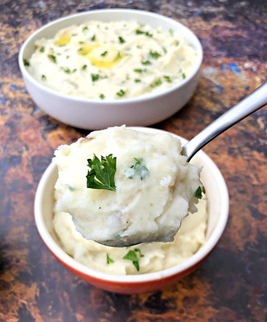 a spoonful of instant pot mashed potatoes with bowls