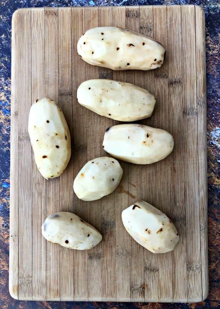 raw potatoes on a cutting board