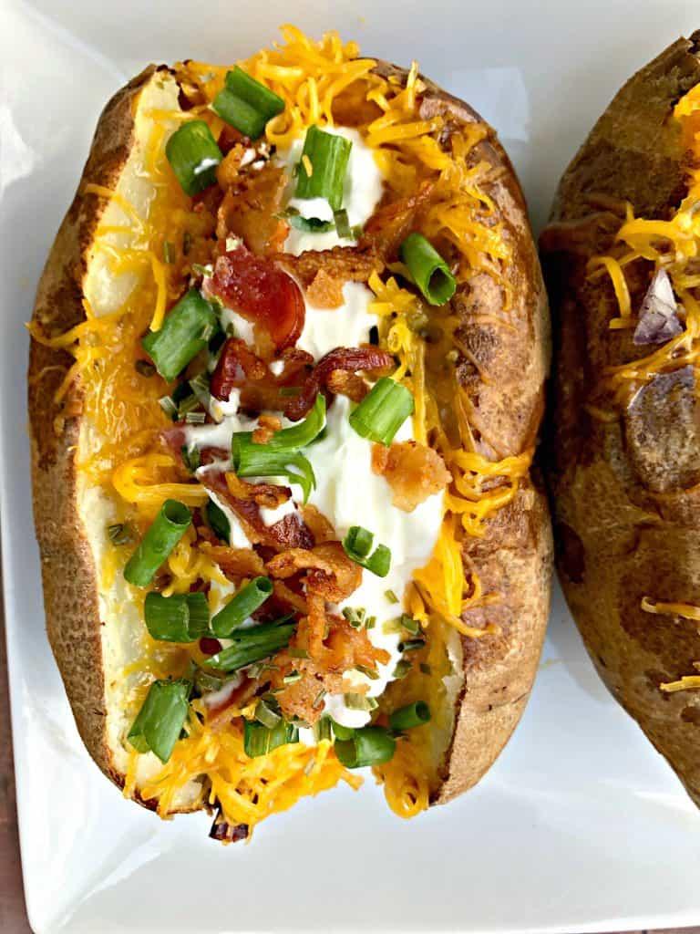 air fryer loaded baked potato on white plate