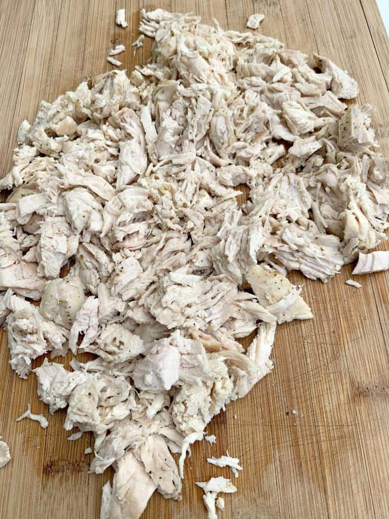 shredded chicken breast on a cutting board