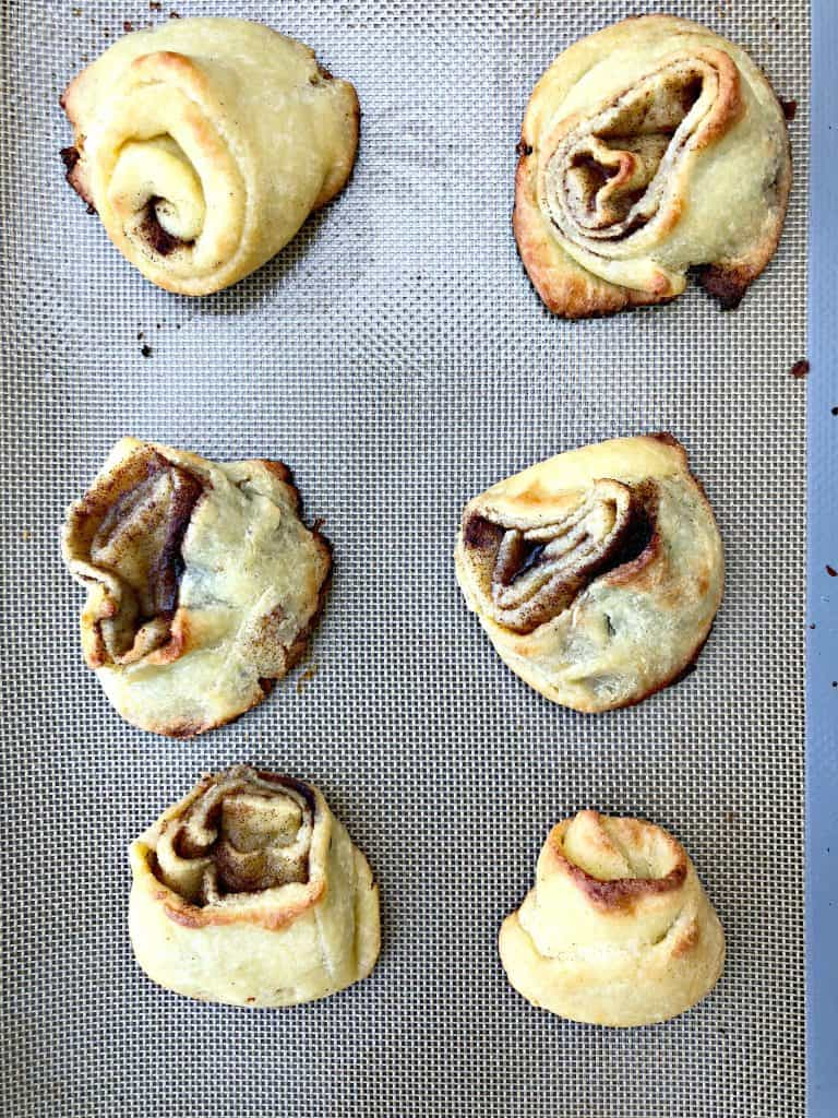 keto fathead cinnamon rolls on a cookie sheet