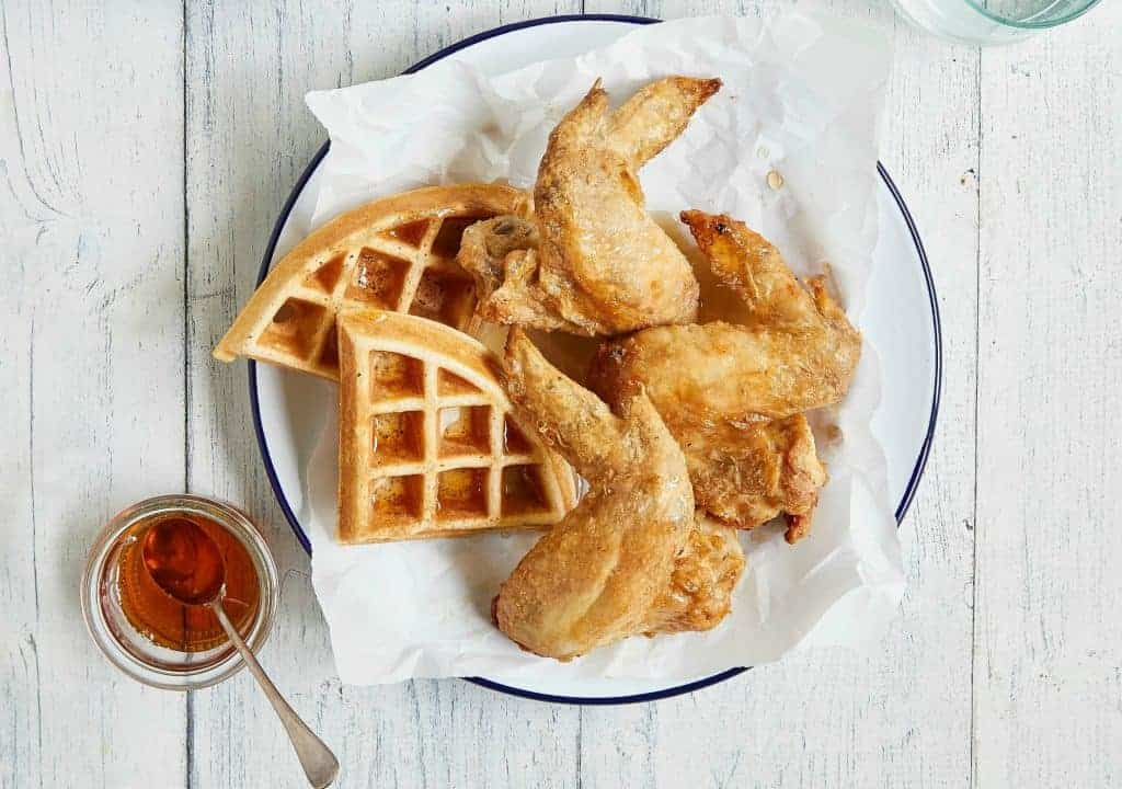 air fryer chicken and waffles on a white plate with syrup