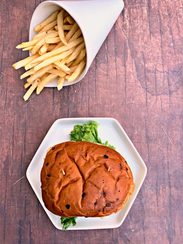 juicy air fryer cheeseburgers on a bun and white plate with fries