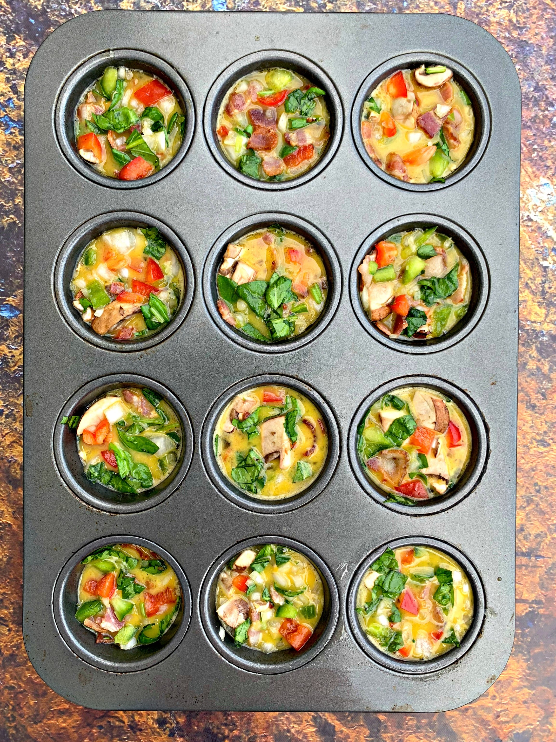 raw eggs with vegetables in a muffin tin