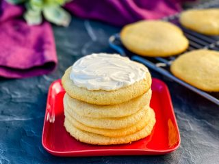 keto low carb sugar cookies on a red plate with cream cheese frosting