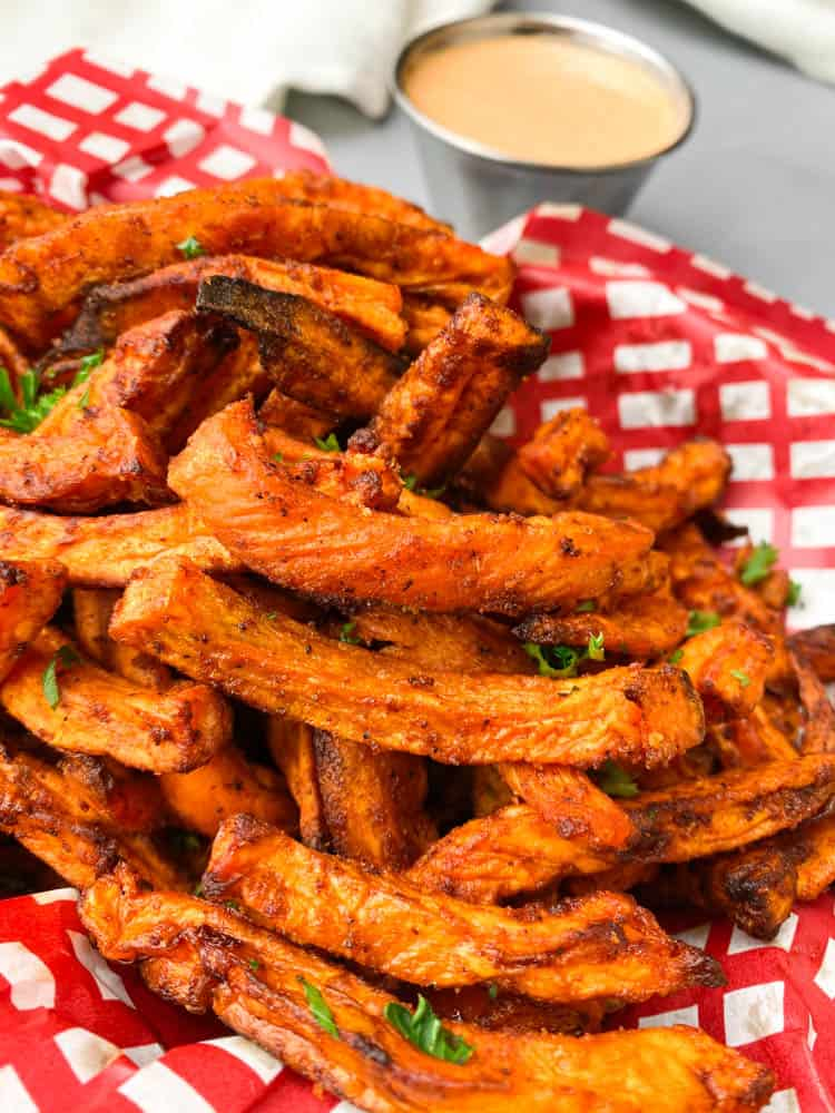 air fryer sweet potato fries in a basket with a red and white napkin